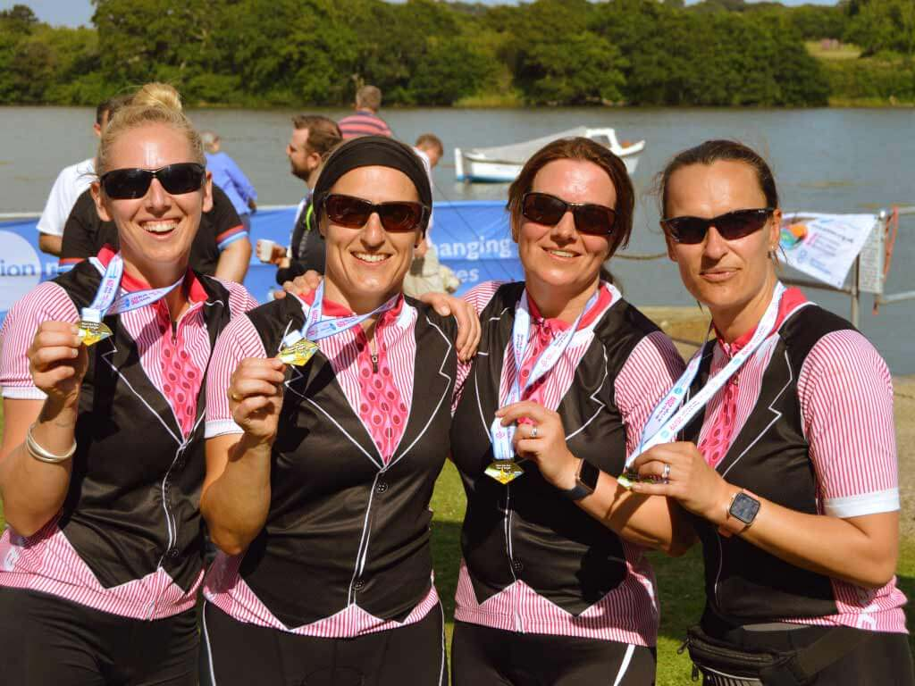 team of four women in matching jerseys holding their medals