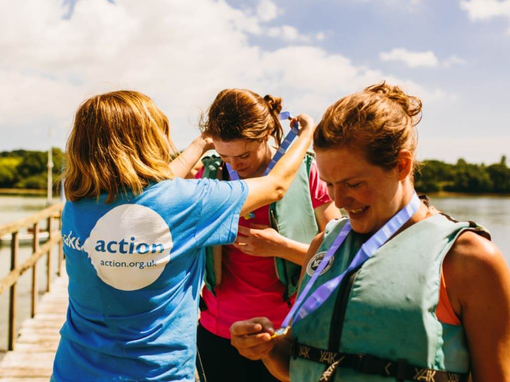 action representative awarding medal to a finisher