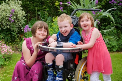 Tom, pictured centre in his wheelchair, with his two sisters